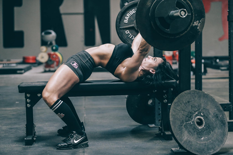 Woman performing bench press with arched back