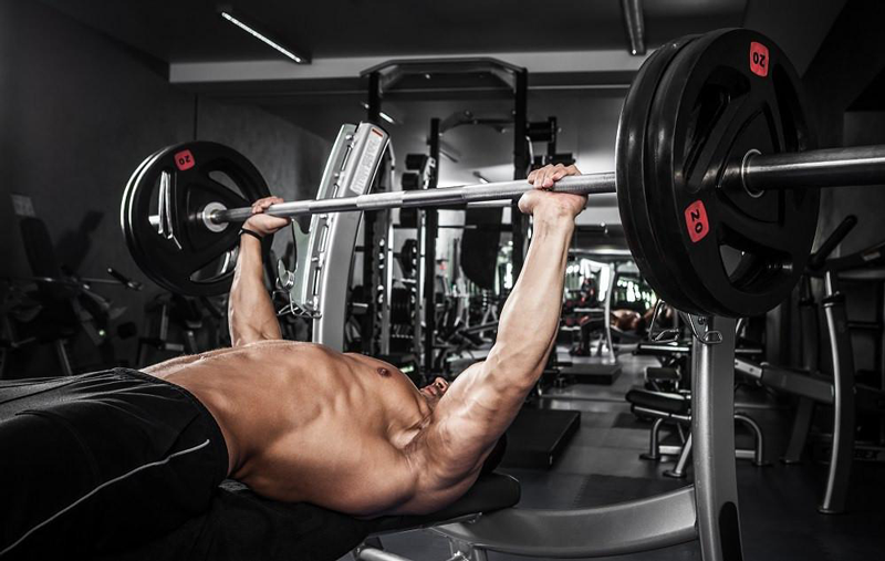 Man with muscular upper body performing bench press
