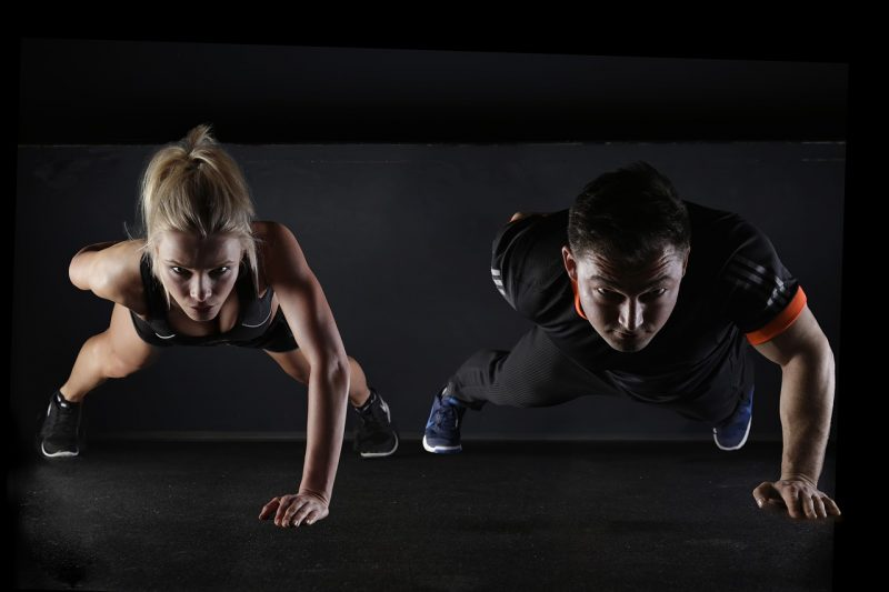 Two people performing single arm push ups as bodyweight exercise