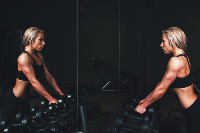 Weight training woman in a gym showing signs of low body fat from body recomposition