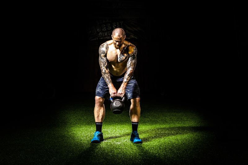 Muscular man performing kettlebell workout
