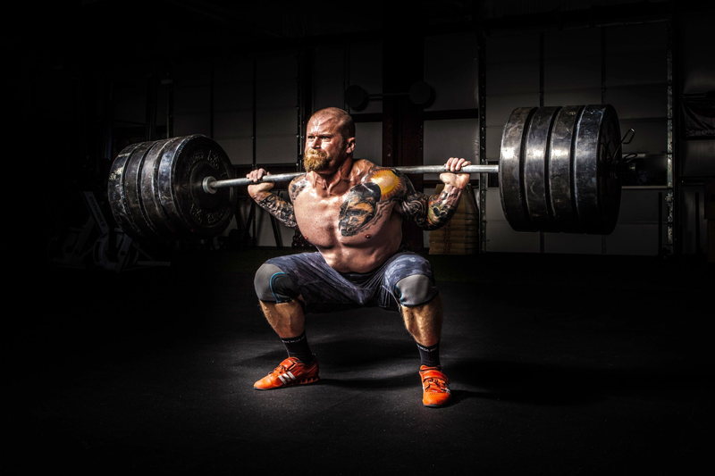 Muscular man bulking by using heavy back squats